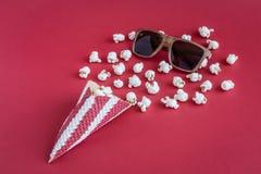 Cono con gli occhiali del cinema e del popcorn sul concetto minimalistic del fondo rosso Fotografie Stock Libere da Diritti
