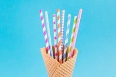 Cono de helado con la paja de papel colorida del manojo dentro, en fondo azul brillante Escena del cumpleaños fotos de archivo libres de regalías