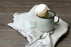 Cono de helado en una taza del esmalte en una tabla de madera Imagen de archivo