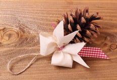 Cono del pino con el arco Imágenes de archivo libres de regalías