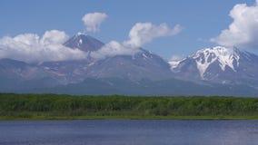 Cono del vulcano attivo, lago alpino, nuvole che vanno alla deriva attraverso il cielo blu vicino al supporto archivi video