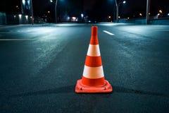 Cono della strada nell'ambito di illuminazione di notte Immagine Stock