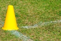 Cono giallo sul campo di erba Fotografie Stock