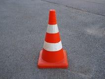 Cono rayado anaranjado del tráfico en una carretera de asfalto fotos de archivo libres de regalías