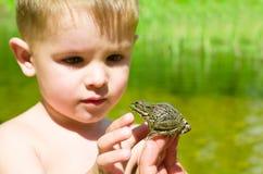 Conocido un niño pequeño con una rana foto de archivo