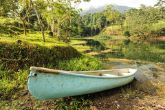 Conoe boat sits next to tropical pond Stock Image