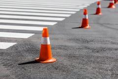 Conos anaranjados del tráfico que se colocan en fila cerca de la cruz peatonal Fotografía de archivo