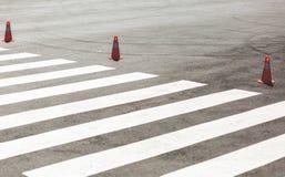 Conos anaranjados del tráfico que se colocan en fila cerca de la cruz peatonal Fotos de archivo