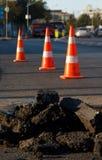 Conos de la construcción y de la seguridad del asfalto Fotos de archivo libres de regalías