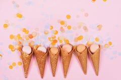 Conos de la galleta del helado con los macarons y confeti en fila en fondo rosado imagenes de archivo