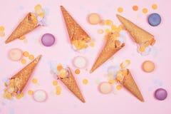 Conos de la galleta del helado con los macarons y confeti en fondo rosado imágenes de archivo libres de regalías