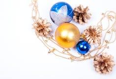 Conos de oro con las bolas de la guirnalda aisladas en blanco Imagenes de archivo