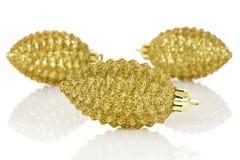 Conos de oro del pino de las chucherías brillantes de la Navidad Imagen de archivo libre de regalías