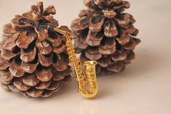 Conos de oro del saxofón y del cedro del alto Invitación del Año Nuevo Imagen de archivo libre de regalías