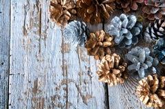 Conos de plata y de oro en el backgound de madera blanco Copyspace Fotografía de archivo libre de regalías