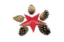 Conos del árbol de abeto y de la estrella roja decorativa del juguete aislados en el fondo blanco Imagen de archivo