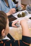 Conos del pino de la pintura del niño pequeño para la Navidad Imagen de archivo