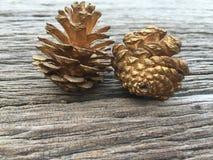 Conos del pino del oro en el fondo de madera Fotografía de archivo libre de regalías