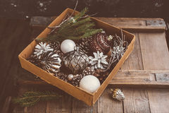 Conos del pino y juguetes del árbol de navidad en la caja Foto de archivo libre de regalías