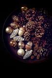 Conos del pino y ornamentos de la Navidad en una bandeja rústica Fotografía de archivo