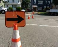 Conos reflexivos anaranjados de la seguridad de tráfico con las flechas Foto de archivo libre de regalías