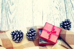 Conos rojos de la caja y de abeto del regalo en una superficie de madera blanca estructural Fotografía de archivo