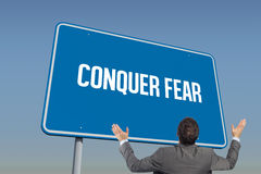 Conquer fear against blue sky. The word conquer fear and businessman posing with arms raised against blue sky Stock Photo
