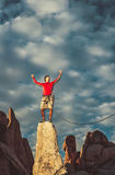 Conquer the mountain. Climber on the summit of a challenging cliff Royalty Free Stock Photos