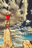Conquer the mountain. Climber on the summit of a challenging cliff Royalty Free Stock Image