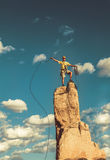 Conquer the mountain. Climber on the summit of a challenging cliff Stock Images