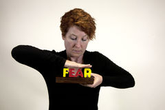 Conquering fear. Woman smashing the word FEAR with her hands royalty free stock images