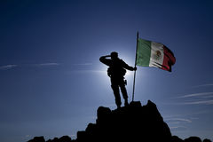 Conqueror with a flag. Soldier on the top of a mountain with a Mexican flag stock photos