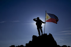 Conqueror with a flag. Soldier on the top of a mountain with a Philippine flag royalty free stock photo