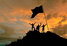 Conquest of height, silhouettes of three people, on top of a mountain, with a flag. Conceptual design. Against the background of the evening sky at sunset with stock images