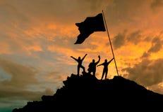 Conquista de la altura, siluetas de tres personas, encima de una montaña, con una bandera Imagenes de archivo