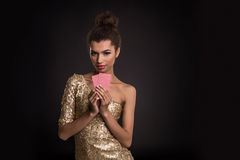 Conquista della donna - la giovane donna in un vestito di classe dall'oro che tiene due carte, una mazza degli assi carda la comb Immagini Stock