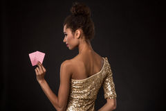 Conquista della donna - la giovane donna in un vestito di classe dall'oro che tiene due carte, una mazza degli assi carda la comb Fotografie Stock Libere da Diritti