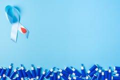 Consapevolezza del nastro blu con goccia rosso sangue e la linea di lancette su un fondo blu, giornata mondiale del diabete fotografia stock