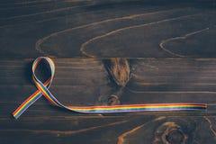 Consapevolezza del nastro dell'arcobaleno per il concetto di LGBT su fondo di legno immagine stock
