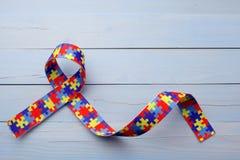 Consapevolezza di autismo del mondo e giorno o mese di orgoglio con il nastro del modello di puzzle su fondo di legno blu immagini stock libere da diritti