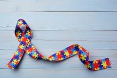 Consapevolezza di autismo del mondo e giorno o mese di orgoglio con il nastro del modello di puzzle su fondo di legno blu fotografie stock libere da diritti