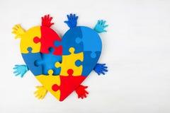 Consapevolezza di autismo di sostegno delle mani del cuore di puzzle fotografia stock