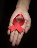 Consapevolezza rossa del nastro sulla mano umana della donna: Giornata mondiale contro l'AIDS Fotografia Stock