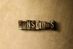 CONSCIENTE - el primer del vintage sucio compuso tipo de palabra en el contexto del metal Fotos de archivo libres de regalías