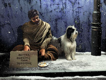Consciousness. Beggar and his dog, sitting on the sidewalk at night, under the falling snow Stock Photos
