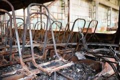 Consecuencias de un fuego en el autobús, accidente Asientos de pasajero chamuscados, piso dañado, negrura alrededor, dentro foto de archivo libre de regalías