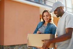 Consegna del pacchetto Donna di Delivering Box To del corriere dell'uomo a casa immagini stock