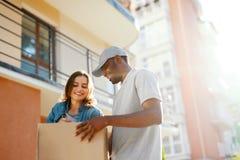 Consegna del pacchetto Donna di Delivering Box To del corriere dell'uomo a casa immagine stock libera da diritti