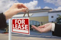 Consegna delle chiavi davanti all'ufficio ed al segno di affari Fotografie Stock