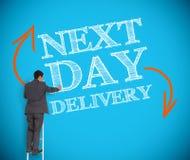 Consegna di giorno successivo di scrittura dell'uomo d'affari su una parete Fotografie Stock